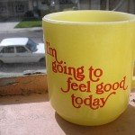 Yellow coffee mug on ledge reads I'm going to feel good today