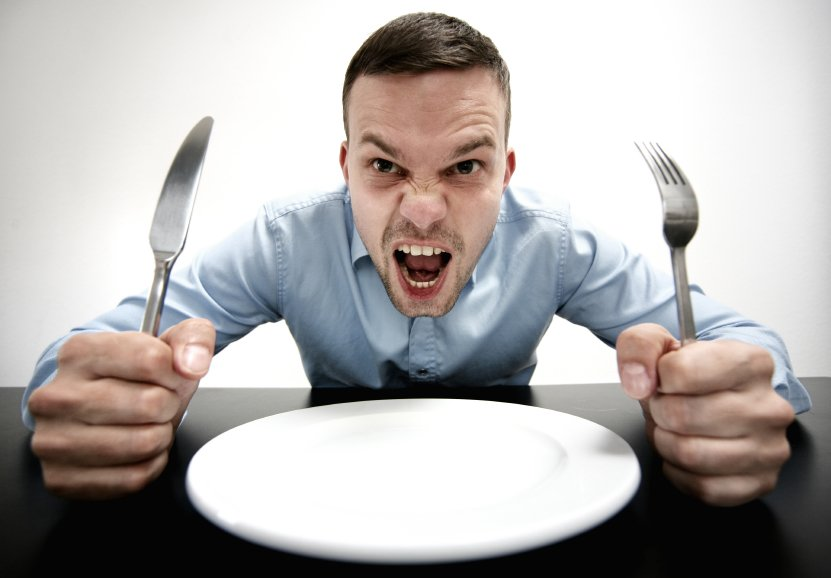 Man holds fork and knife with empty plate and angry look on face