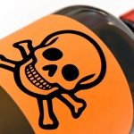 A brown bottle with orange label of skull and bones