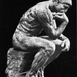 Stone statue of The Thinker with black background