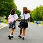 Rear view of two school girls walking down street holding hands