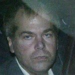 John Hinckley in the back of a cop car with angry expression