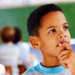 Young boy ponders with classroom classmates in background