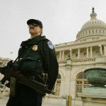Homeland Security officer stands guard with rifle