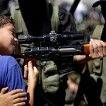 Young boy is shown how to hold rifle