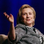 Hillary Clinton smiling with hands up during speech