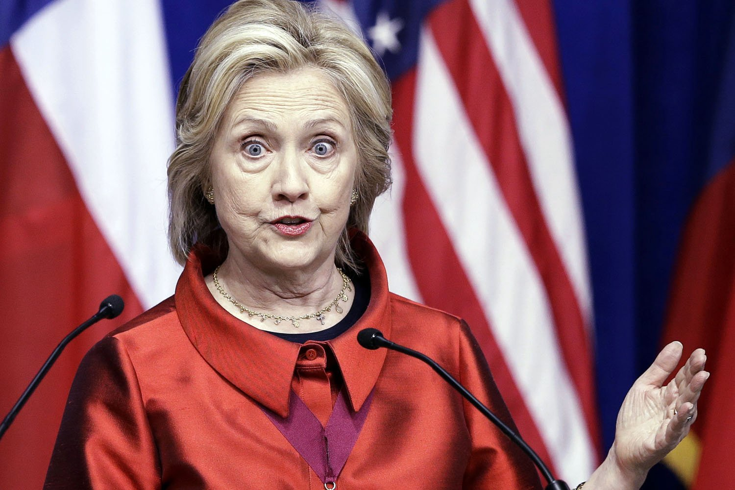 Hillary Clinton in red attire gives speech with serious facial expression