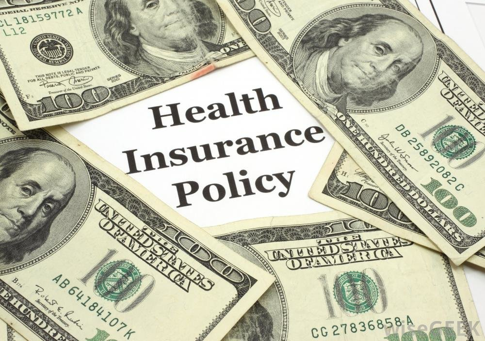 The words Health Insurance Policy surrounded by multiple 100-dollar bills