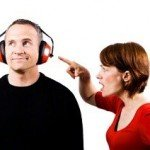 Woman points at man's face as man listens to headphones