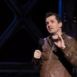 Comedian Jim Jeffries in brown leather coat performs live