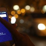 Woman using Uber private driver app with city lights in background