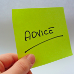 A hand holds green post it note with the word Advice underlined