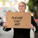 Man in suit holds cardboard sign that reads Please Like Me!