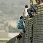Immigrants climbing over Mexican border