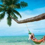 Woman relaxes in hammock from a palm tree