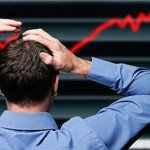 Man stands holding head in frustration at stock market decrease