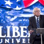 Sanders standing at podium with Libery University logo behind him