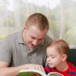 A man reads to young child