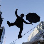 Man wearing tophat with umbrella walks on tightrope