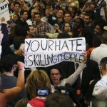 """A protestor holds up a sign reading """"Your Hate is Killing People""""  in the midst of Republican U.S. presidential candidate Donald Trump's campaign rally in New Orleans, Louisiana March 4, 2016.   REUTERS/Layne Murdoch Jr.  - RTS9DQN"""
