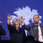 Democratic presidential candidate Hillary Clinton holds her hands up in a group prayer, led by Rev. Isaac Holt, pastor of the Royal Baptist Church, left, at the conclusion of a campaign event at the Royal Baptist Church Family Life Center in North Charleston, S.C., Thursday, Feb. 25, 2016. Second right is North Carolina state Sen. Marlon Kimpson, and right is emcee and local television personality Marjorie Bright Matthews. (AP Photo/Gerald Herbert)