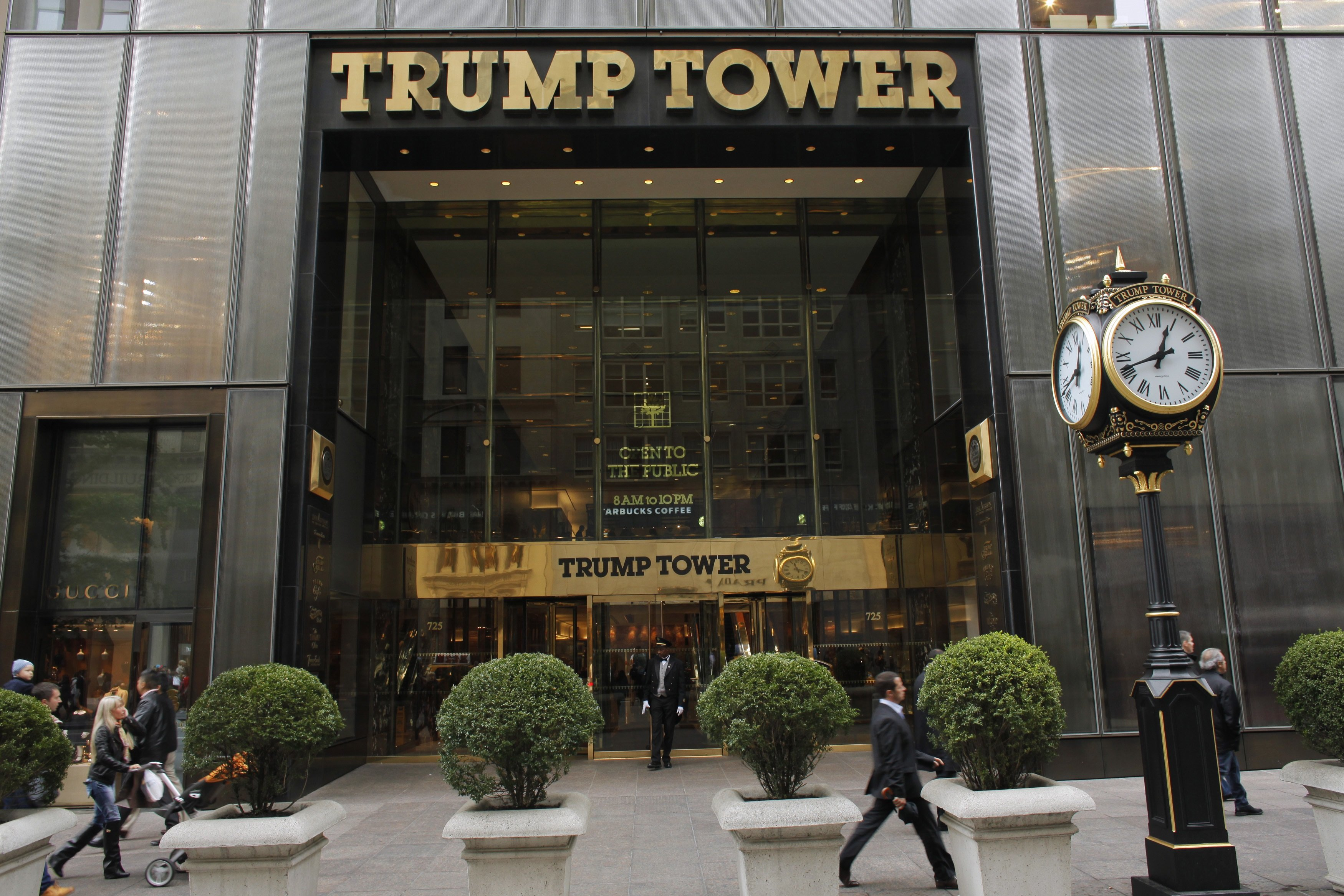 People walk in front of the Trump Tower in New York October 24, 2012.  Donald Trump offered to pay $5 million to the charity of President Barack Obama's choice if Obama releases his college and passport records, the real estate mogul and television personality said on Wednesday. REUTERS/Eduardo Munoz (UNITED STATES - Tags: POLITICS BUSINESS) - RTR39J4Q